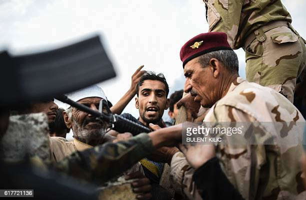 TOPSHOT An Iraqi man reacts as families who were displaced by the ongoing operation by Iraqi forces against jihadists of the Islamic State group to...
