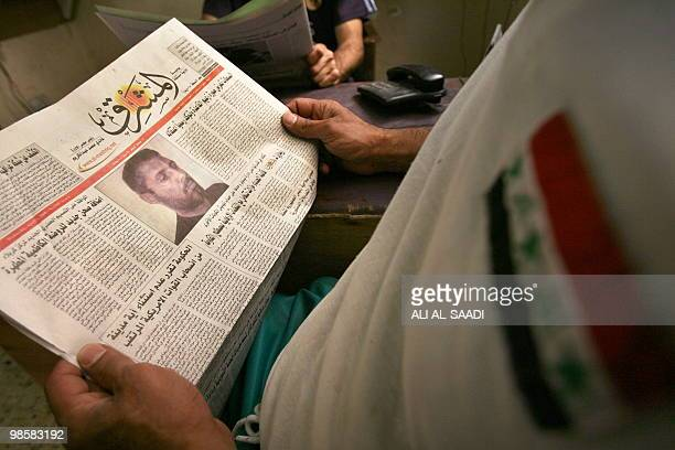 An Iraqi man reads an article picturing a man authorities claim is Abu Omar alBaghdadi said to be the leader of the AlQaeda umbrella group in Iraq on...