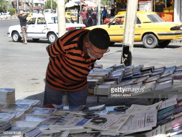 An Iraqi man reads the headlines at a newspaper stand in the capital Baghdad on August 29 2018 Iraq's parliament will meet next week for its first...