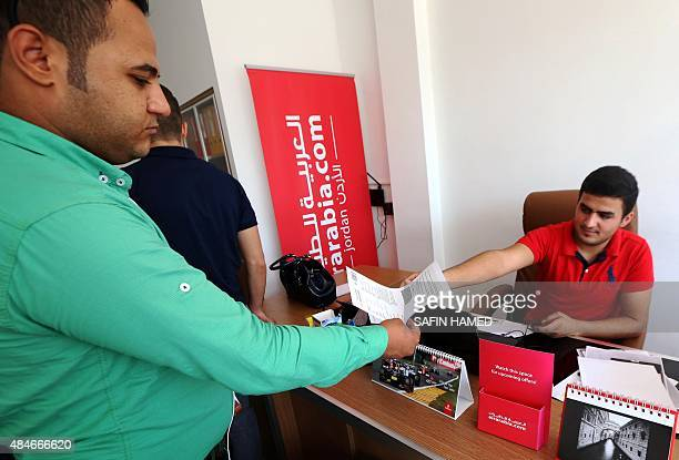 An Iraqi man receives a copy of his ticket at a travel agent's office in Arbil the capital of the autonomous Kurdish region on August 13 2015 Arbil...
