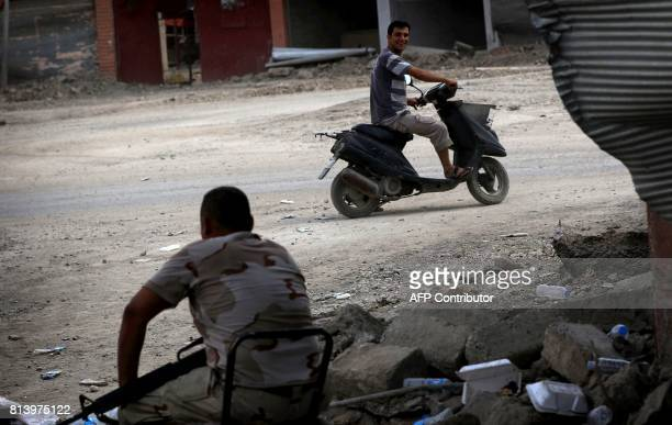 An Iraqi man rides a scooter past a member of the Iraqi forces in west Mosul on July 13 a few days after the government's announcement of the...