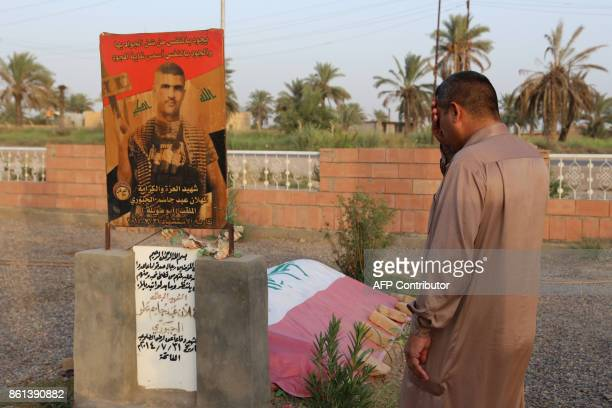 An Iraqi man ries as he visits the grave of a relative who was killed during battles with Islamic State group fighters at a graveyard in the Iraqi...
