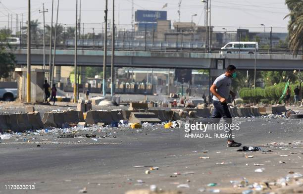 An Iraqi man runs as protesters try to demonstrate for the forth day against state corruption, failing public services, and unemployment in the Iraqi...