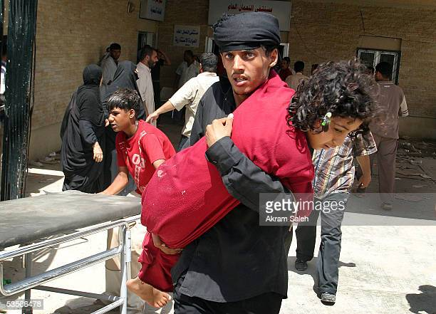 An Iraqi man rushes to the hospital as he carries a girl injured in the stampede August 31, 2005 in Baghdad, Iraq. As many as 650 people, mostly...