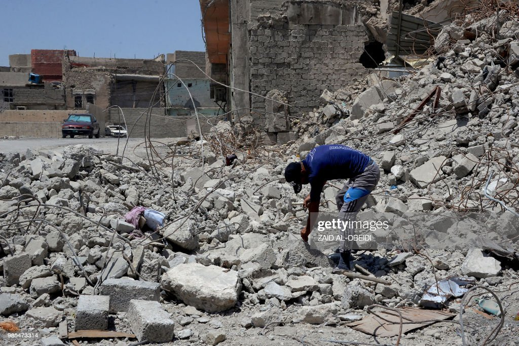 An Iraqi man searches the debris in Mosul on June 27, 2018. - Nearly a year after the Islamic State group was expelled from its 'capital' in Iraq, hundreds of vehicles on Wednesday began the titanic task of clearing the rubble in the western part of Mosul, the most destroyed city in the country.