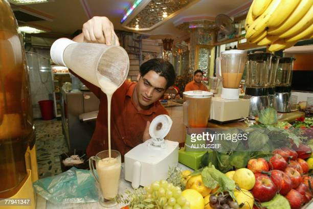 An Iraqi man serves fruit cocktails at a juice bar in central Baghdad's alKarrada neighborhood late 11 November 2007 Declines in Iraqi civilian and...
