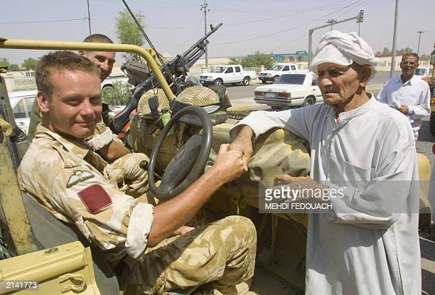 An Iraqi man shakes hands with a patrolling British soldier after chatting with him in the southern town of Amara some 200 kms north of Iraq's second...