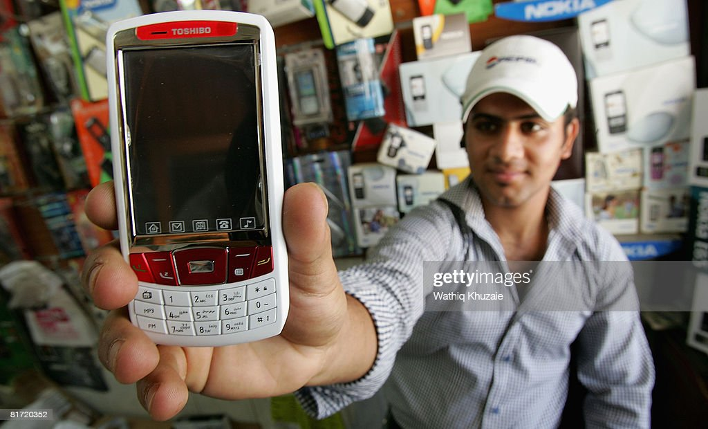An Iraqi man shows a mobile phone on June 26, 2008 in Baghdad, Iraq. The war-damaged aging landline telephone infrastructure means Iraqis are increasingly more dependent on mobile phones in daily life and business.