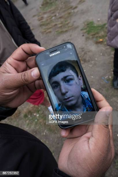 CAMP KRNJACA BELGRADE SERBIA An Iraqi man shows pictures of his son after he was assaulted by the Bulgarian police With Hungary and Croatia stopping...