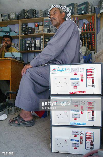 An Iraqi man sits by electrical appliances converting direct to alternating current at Agd alNasara market specialized in selling electricity...