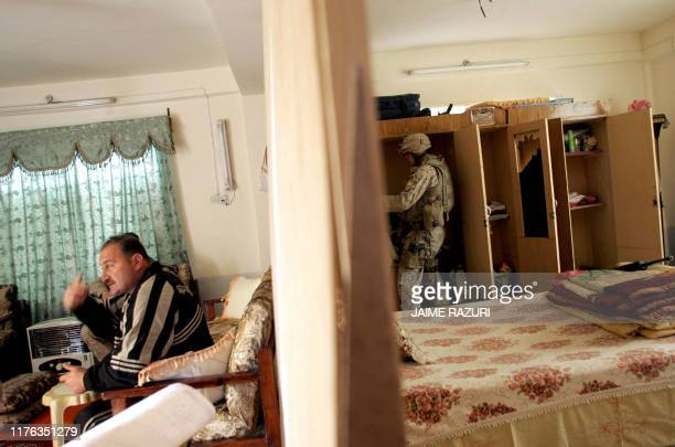 An Iraqi man sits in the living room as a US Marine from the 1st Battalion searches a bedroom during a search patrol in the town of Haditha, west of...