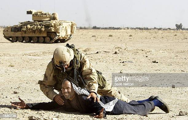 An Iraqi man smiles as he is searched by a US Army 3rd Division 37 Infantry soldier during a search and destroy mission March 27 2003 near the town...