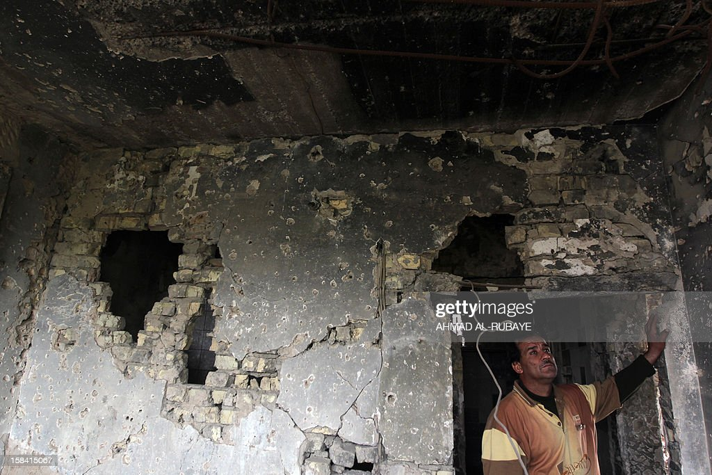 An Iraqi man stands at his house destroyed by a US air strike in 2008 as the US army was fighting radical Shiite cleric Muqtada al-Sadr's Mahdi militia in Baghdad's Sadr City on December 10, 2012. A US-led coalition invaded Iraq in 2003, toppling dictator Saddam Hussein and beginning a conflict that cost the lives of tens of thousands of Iraqis, thousands of Americans and hundreds of billions of dollars. Almost 10 years later and after that the last convoy of American armoured vehicles rolled across the border into Kuwait on the chilly morning of December 18, 2011, many Iraqis still lack basic services such as consistent electricity and clean water, and though levels of violence are down, insurgents continue to carry out bombings and shootings almost every day.