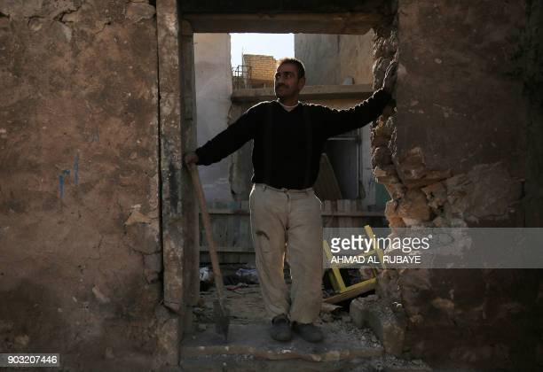 An Iraqi man stands at the entrance of his house in Mosul's Old City on January 8 as a few people venture to return to their homes in the...