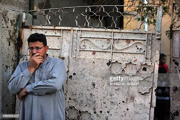An Iraqi man stands in front of a door covered with shrapnel and blood stains after a suicide bomber reportedly blew himself up in the midst of a...