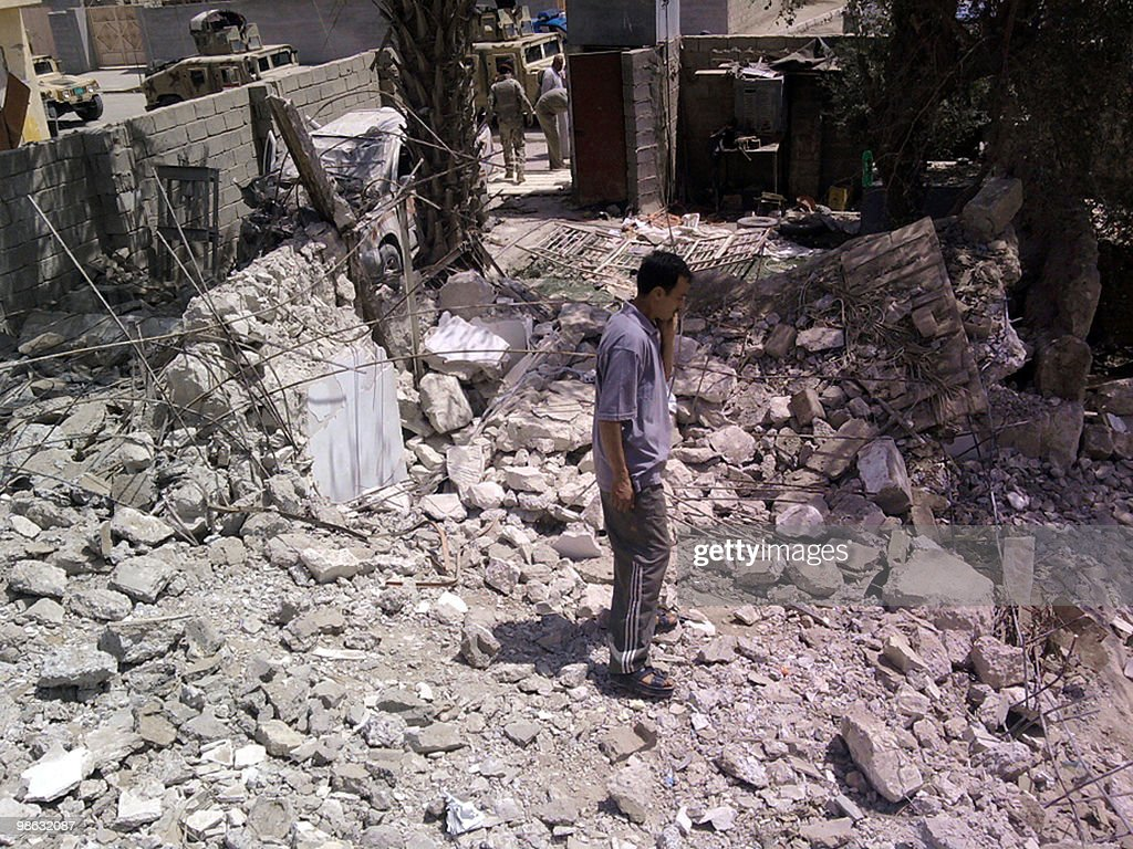 An Iraqi man stands in the rubble after