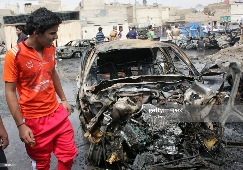 An Iraqi man stands near a car damaged in a car bomb explosion in Sadr city on April 23, 2010 in Baghdad, Iraq. A series of bombings rocked a market and Shiite mosques as worshippers departed Friday Prayer services, killing at least 60 people and wounding many more.