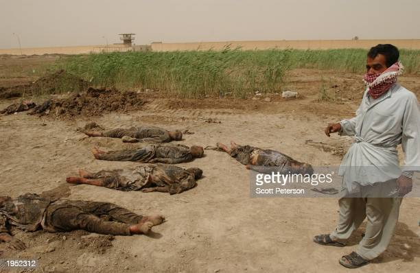 An Iraqi man stands near recently buried bodies in the compound of Iraq's notorious Abu Ghraib prison April 25 2003 in Abu Ghraib Iraq These corpses...