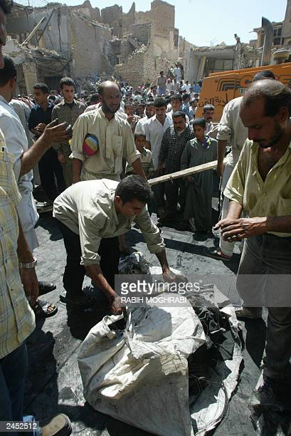 An Iraqi man tidies up a bundle containing remains and clothing removed from the vehicles carrying assassinated top Shiite leader Ayatollah Mohammad...