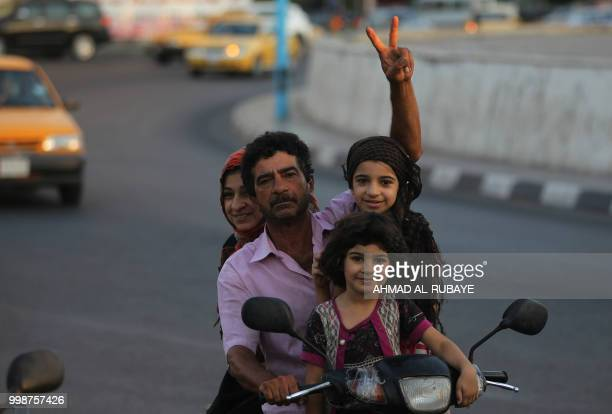 An iraqi man transporting his family on a motorbike flashes the victory sign in the capital Baghdad's Tahrir Square during demonstrations against...