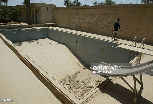An Iraqi man walks 19 June 2003 past a mural decorating a wall surrounding a swimming pool Iraqi men walk 19 June 2003 in the home of toppled leader...