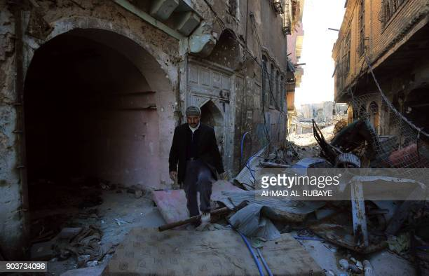 TOPSHOT An Iraqi man walks amidst waste in a alley in the old city of Mosul on January 9 2018 Along the waterfront of the Tigris River in Iraq's...