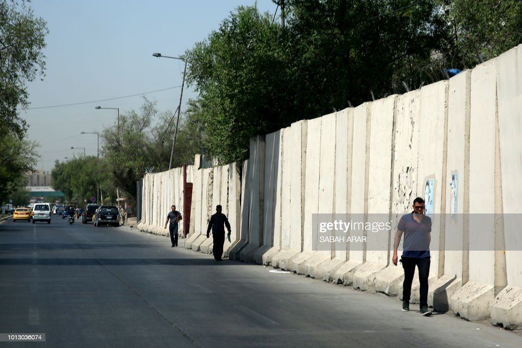 An Iraqi man walks by T-walls' cement blocks in Baghdad on