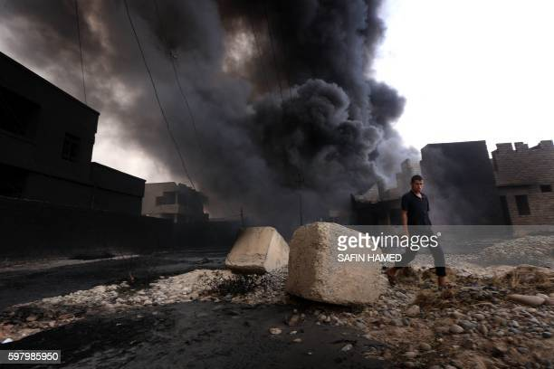 TOPSHOT An Iraqi man walks near smoke billowing from oil wells set ablaze by Islamic State group militants before fleeing the oilproducing region of...