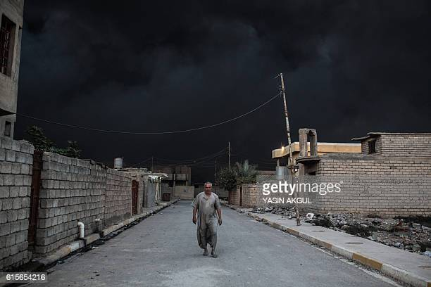TOPSHOT An Iraqi man walks on a street covered with smoke after a fire from oil was set ablaze in the Qayyarah area some 60 kilometres south of Mosul...