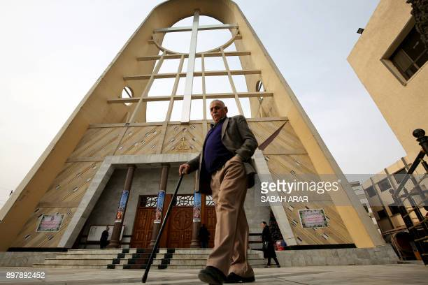 An Iraqi man walks outside the Syriac Catholic Church of Sayedat alnajat in the capital Baghdad on December 24 2017 following a Christmas mass / AFP...