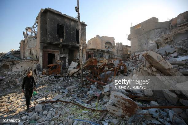 An Iraqi man walks over the rubble in the old city of Mosul on January 9 2018 Along the waterfront of the Tigris River in Iraq's wartorn Mosul gaping...