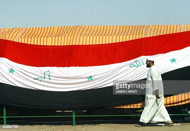 An Iraqi man walks past a huge Iraqi flag draped on a tent setup just outside the Abu Ghraib prison west of the capital Baghdad on the second day of...