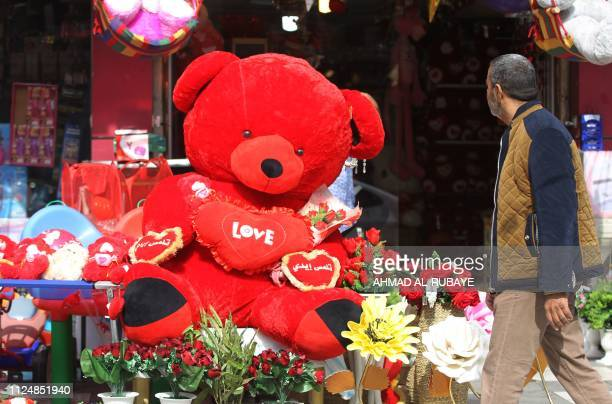 An Iraqi man walks past a shop in central Baghdad decorated with Valentine Day's paraphernalia on February 14 2019