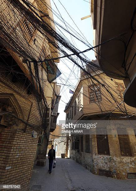 An Iraqi man walks under tangled electricity wires in the old quarter of the capital Baghdad on February 18 2015 Since the USled invasion on Iraq in...
