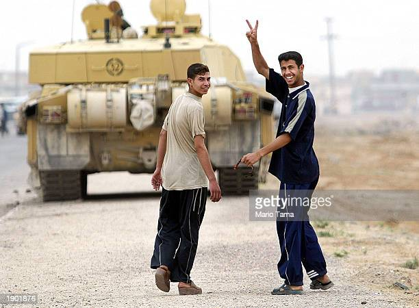 """An Iraqi man waves the """"peace"""" sign outside the University of Basra in front of a British tank while fighting continues in the city April 7, 2003 in..."""