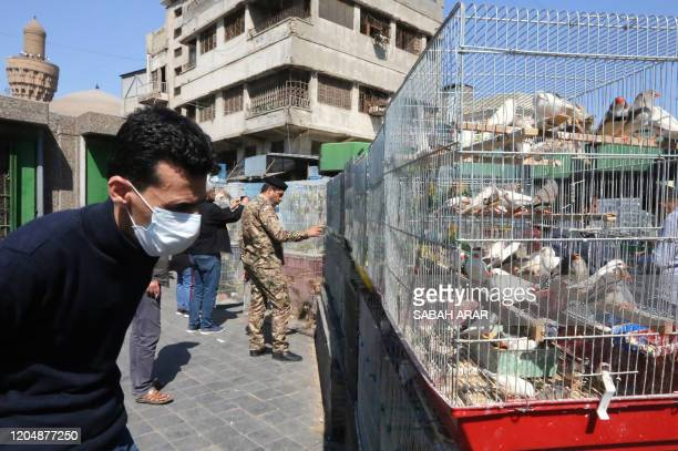 An Iraqi man wearing a protective mask looks at birds displayed for sale in a cage at Baghdad's AlGhazel bird market on March 3 2020 as the number of...