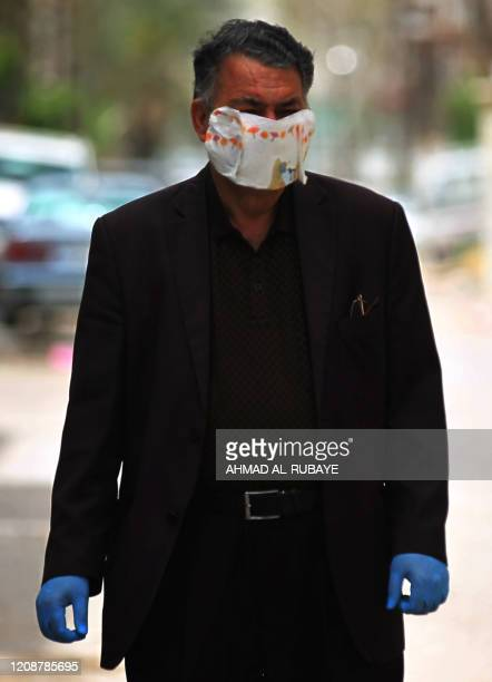 An Iraqi man wearing gloves and a makeshift mask walks in Baghdad's Zayoun area on April 1, 2020 amid measures to limit the spread of the COVID-19...