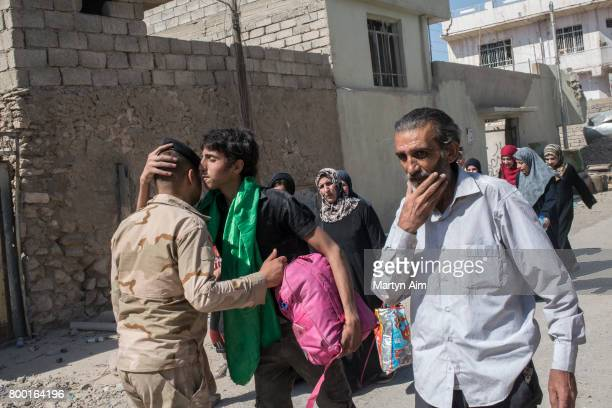 An Iraqi man wearing the green scarf of the Shi'ite faith kisses an Iraqi Army soldier on safely reaching the Iraqi forces position as Iraqi...