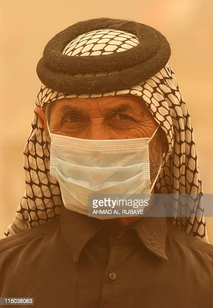 An Iraqi man wears a surgical mask for protection from a heavy sandstorm that is blanketing Baghdad on June 2 2011 AFP PHOTO/AHMAD ALRUBAYE