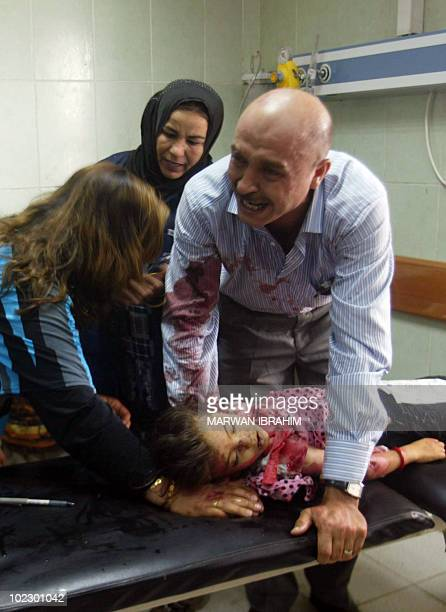 An Iraqi man weeps at a hospital in Kirkuk over the body of his daughter who was killed in one of two car bomb explosions on June 18 targeting a...