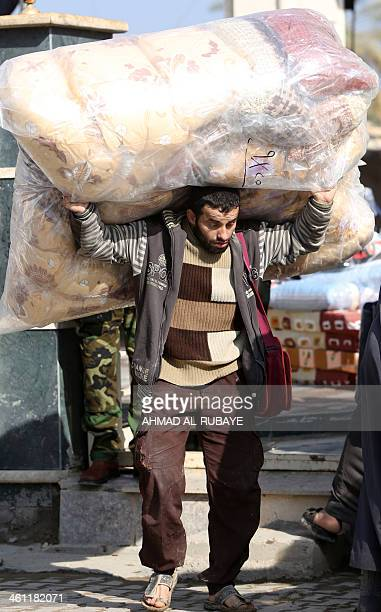 An Iraqi man who fled Fallujah with his family carries blankets distributed by the International Organization for Migration NGO on January 6 2014 in...