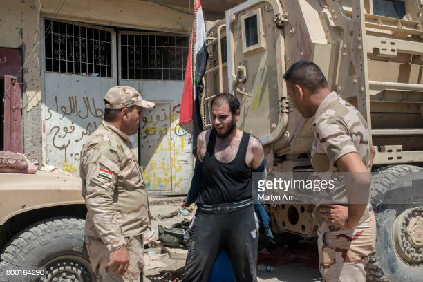 An Iraqi man who has fled the Islamic State controlled Old City of west Mosul where heavy fighting continues is questioned and searched believed to...