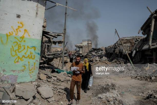 An Iraqi man with his wife carries his baby through the Old City of west Mosul in front of the destroyed alNuri mosque where heavy fighting continues...