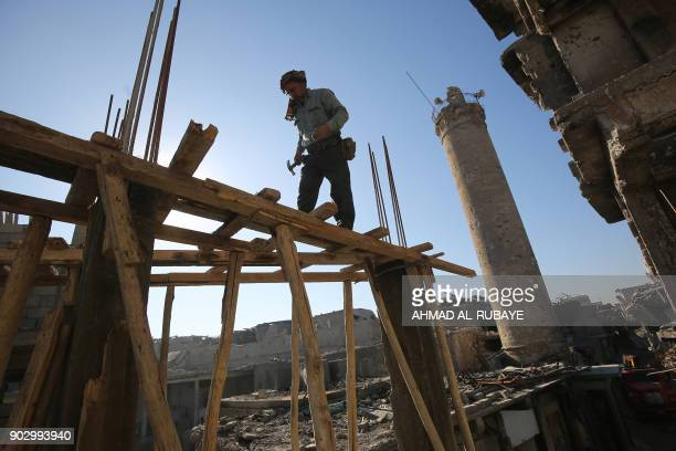 TOPSHOT An Iraqi man works on a damaged house in Mosul's Old City on January 8 six months after Iraqi forces seized the country's second city from...