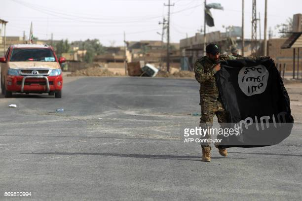 An Iraqi member of the Hashed alShaabi carries an upsidedown Islamic State group flag in the city of alQaim in Iraq's western Anbar province near the...