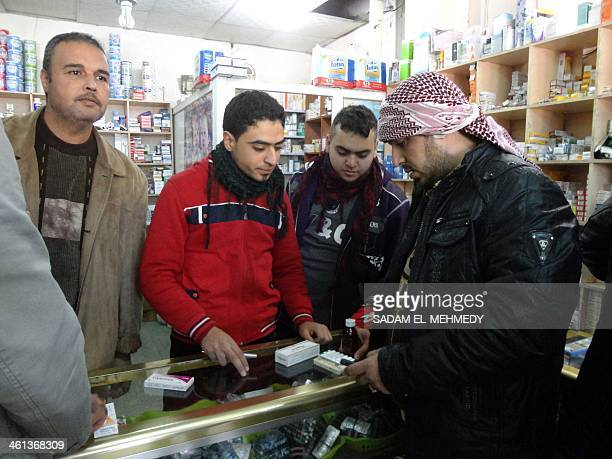 An Iraqi men queue at a pharmacy to be served in the center of the city of Fallujah, west of the capital Baghdad on January 8 following days of...