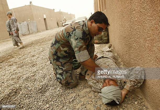 An Iraqi military rescue officer checks the pulse of a comrade during a training session on emergency rescue at the old Muthana airport in Baghdad on...