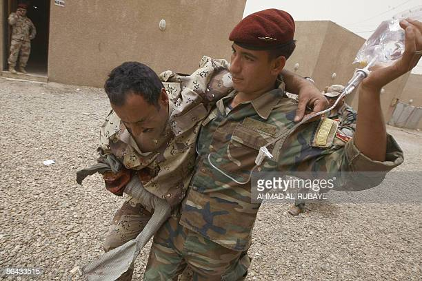 An Iraqi military rescue officer helps a comrade pretending to be injured during a training session on emergency rescue at the old Muthana airport in...