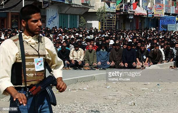 An Iraqi militiaman , loyal to radical Shiite cleric Moqtada al-Sadr, provides security as Iraqi Shiites attend a Friday prayer service March 3, 2006...