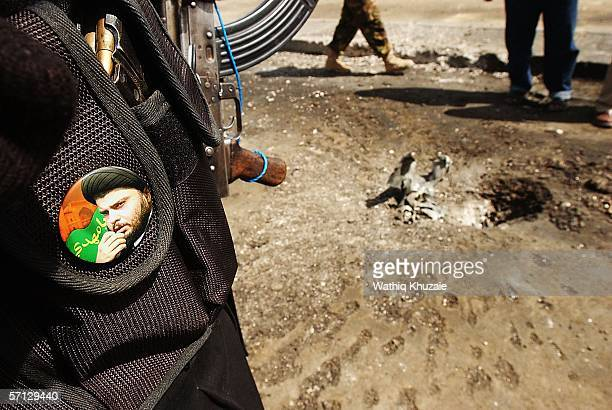An Iraqi militiaman loyal to the radical Shiite cleric Moqtada alSadr inspects a crater caused by a mortar attack as a picture of alSadr is seen on...